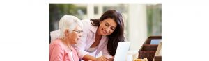 Woman Helping an Older Lady Use a Laptop